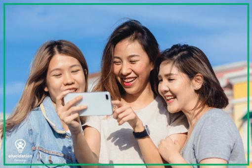 teenage girls looking at phone
